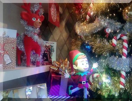 Elf dn reindeer beside their Christmas tree
