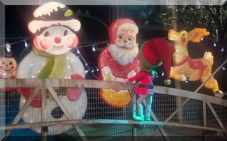 elf looking at Santa, a snowman and reindeer decroations