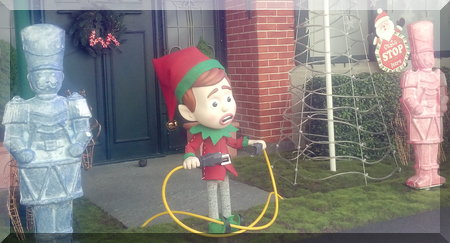 elf holding the ends of a power cord in front of a house
