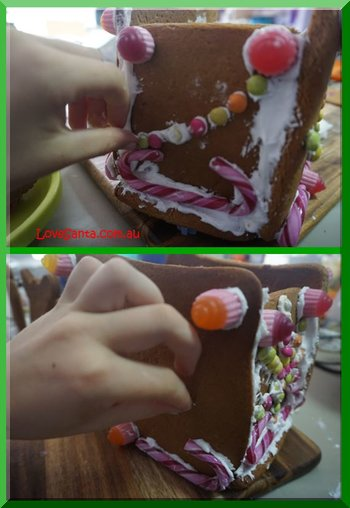 CHild's hand attaching lollies to a gingerbread sleigh