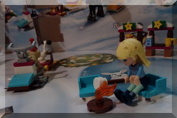 Lego girl sitting at a campfire toasting marshmallows