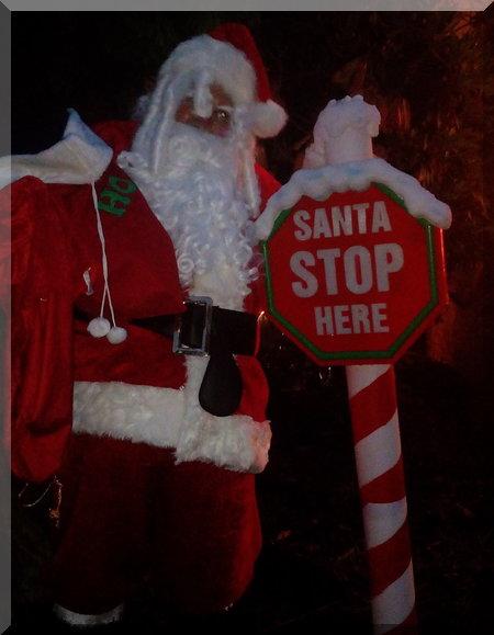 Santa beside a 'Santa stop here' sign