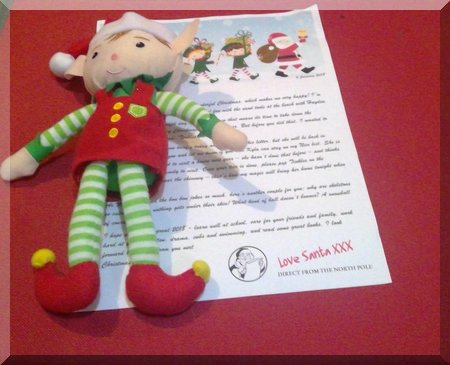 Elf lying on a letter from Santa