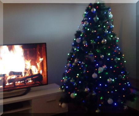 CHriChristmas tree beside a roaring fire