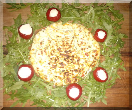 baked cheese surrounded by green leaves to form a Christmas wreath