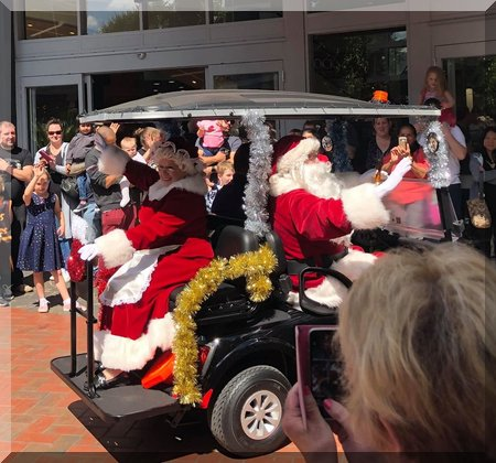 Santa and Mary Claus arriving in a tinsel cover buggy