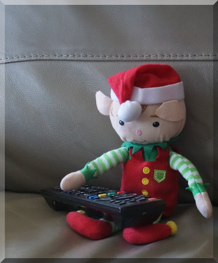 Christmas elf relaxing on couch with a remote control