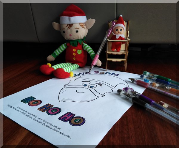 Christmas elf colouring in a Love Santa picture