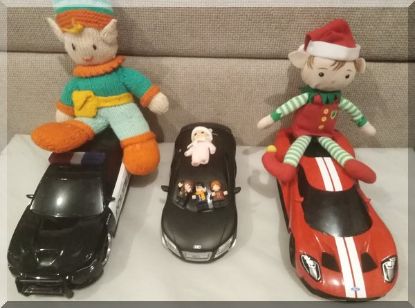 three elves seated on remote control cars