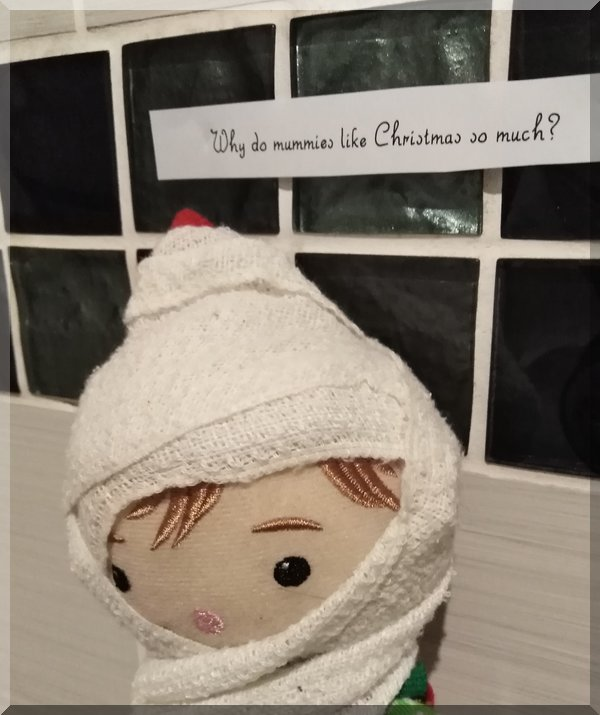 Tinkles the Christmas Elf wrapped as a mummy,asking why do mummies love Christmas