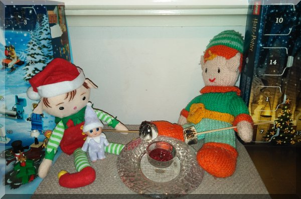 Christmas and Tooth Elves toasting marshmallow on a Christmas candle