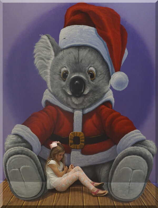 Large koala in Santa outfit cuddling young girl