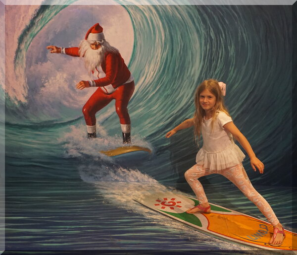 Santa and a girl on surf boards in a wave tunnel
