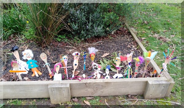 Set of colourful spoon people in a kinder garden bed