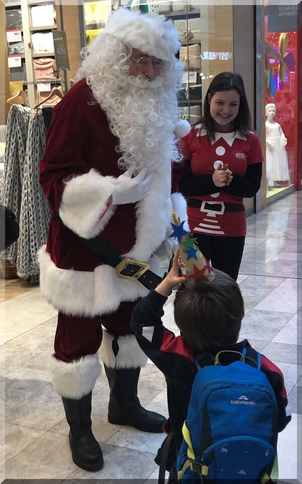 Santa and elf talking to a child in a shopping centre