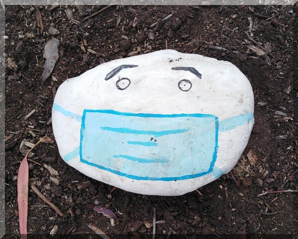 A white rock with eyes and a blue mask painted on