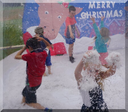 Children playing in fake snow in a summer Christmas