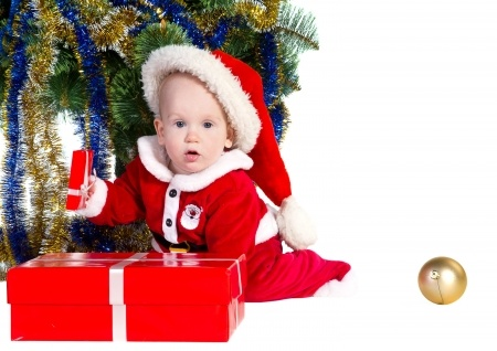 baby in santa suit and hat holding a gift under a Christmas tree