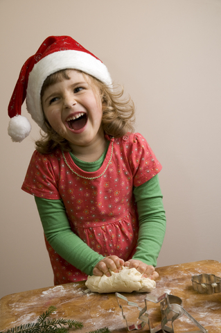 Girl in Santa hat cooking and laughing