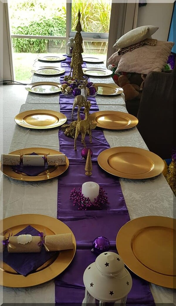 Purple and gold themed table setting with reindeer centrepieces