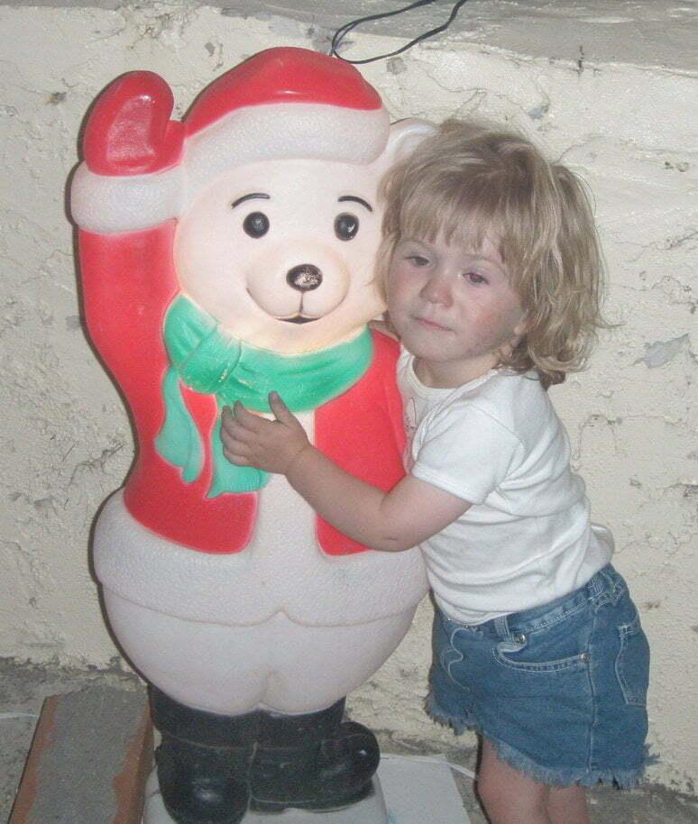 Young girl nervously hugs a Christmas snow bear
