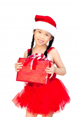 Girl in red Santa outfit holding a gift