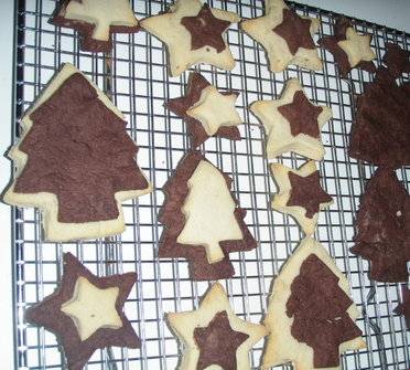 Star and Christmas tree biscutis cooling on a tray
