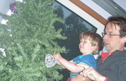 Yong boy and Dad hang an ornament on a Christmas tree