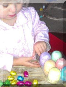 little girl with chalk & chocolate easter eggs