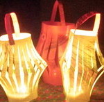 Three child-made paper lanterns lit by candles