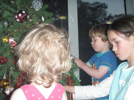 three children decorating a Christmas tree at home