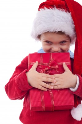 Boy in a Snat hat giving a Christmas gift