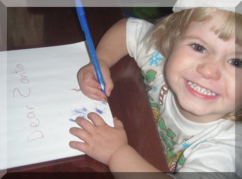 Smiling little girl writing a letter to Santa