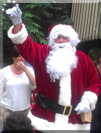 Santa holding bells and a cardboard gift