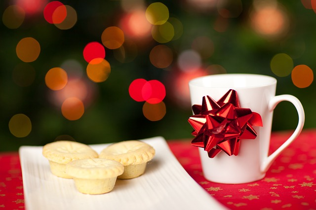 Chirtsmas bow on a mug beside a plate of mince pies