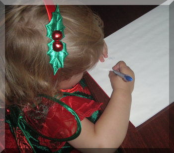 Little girl dressed for Christmas and writing on blank paper