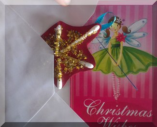 Child putting a cotton bud star and Crhsitmas card into an envelope