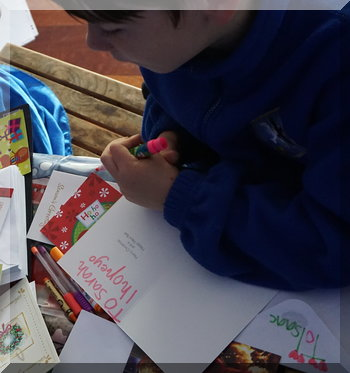 Boy writing in Christmas cards with childish writing