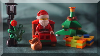 Lego Santa beside two Christmas trees