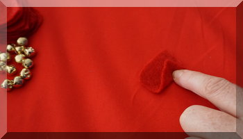 fingers folding red felt to make a petal