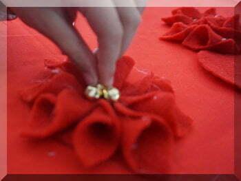 small hand adding bells to a felt flower