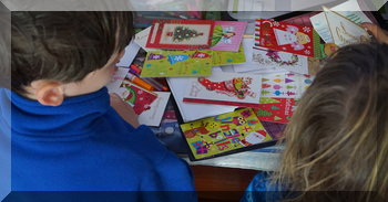 Two children looking at Christmas cards