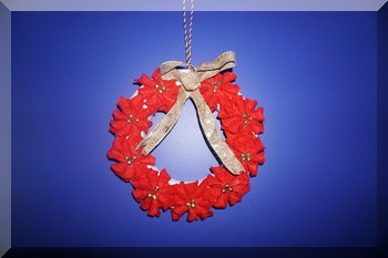 Felt poinsettia wreath handing on a blue wall