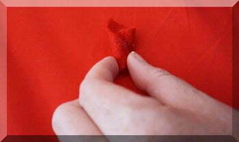 fingers holding red felt petal