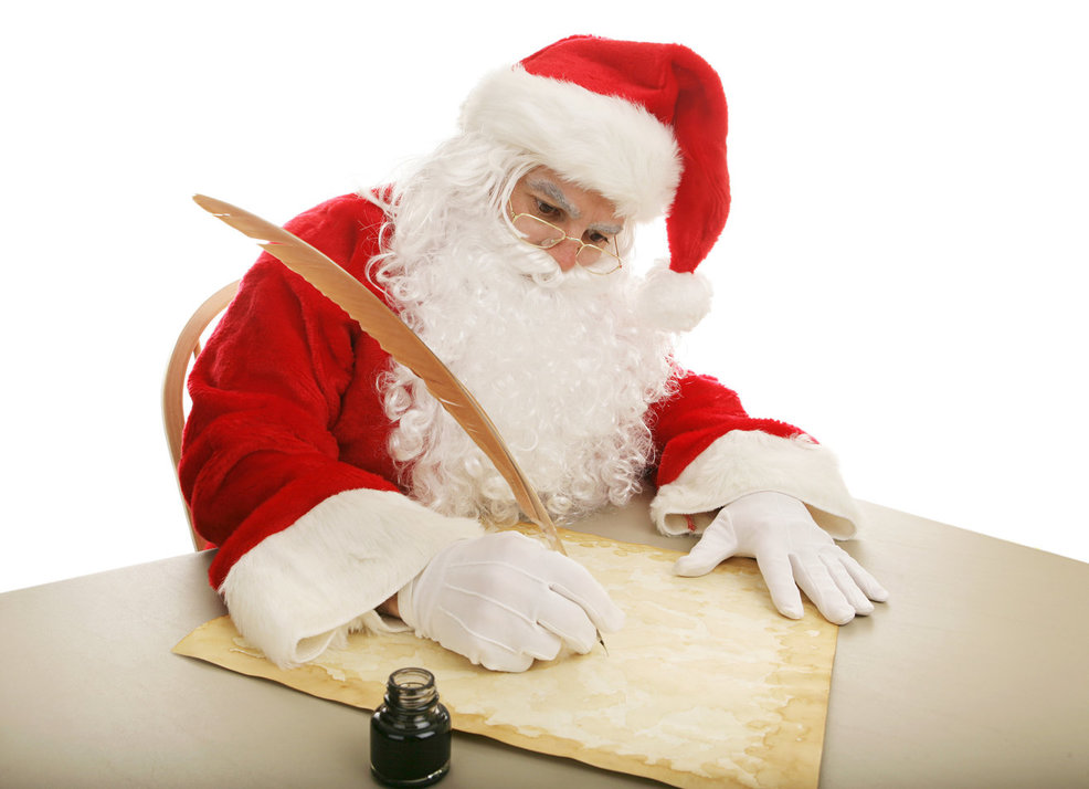 Santa writing on parchment with a large quill