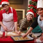 boy and two women cooking Christmas treats in Santa hats