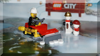 A fire fighter driving a snow plough in Lego City.