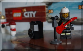 Lego Firefighter holding guitar in front of microphone/