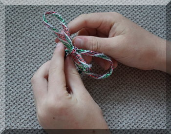 child's hands with a finished Christmas ribbon bow