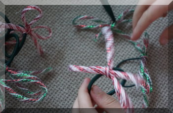 child adding finished CHristmas hair tie to a pile of hair ties